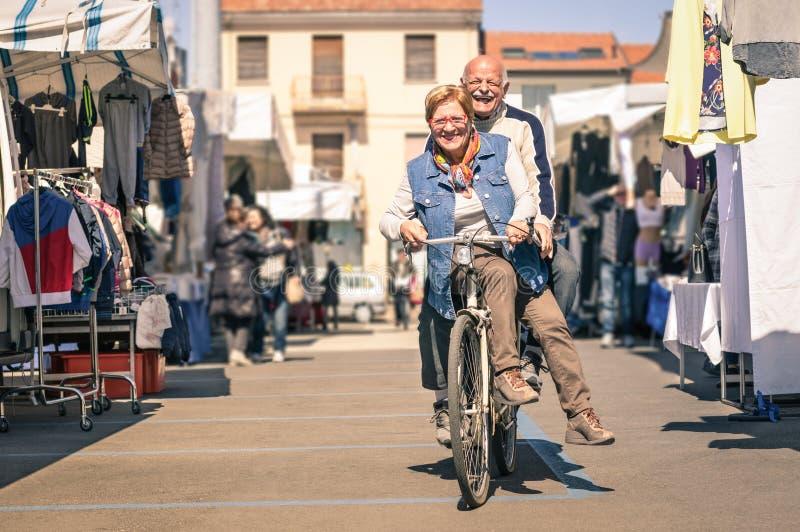 Glückliche ältere Paare, die Spaß mit Fahrrad an der Flohmarkt haben lizenzfreies stockfoto