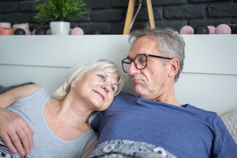 Glückliche ältere Paare, die zusammen im Bett liegen lizenzfreie stockbilder