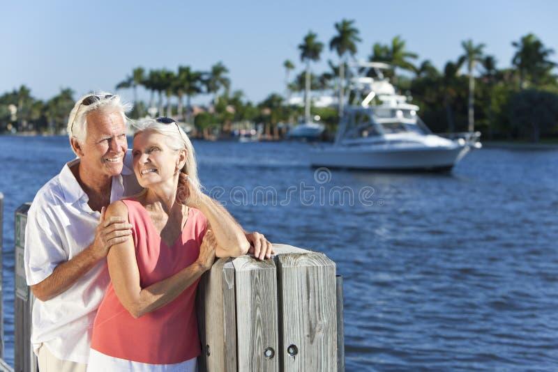 Glückliche ältere Paare durch River oder Meer mit Boot lizenzfreies stockbild