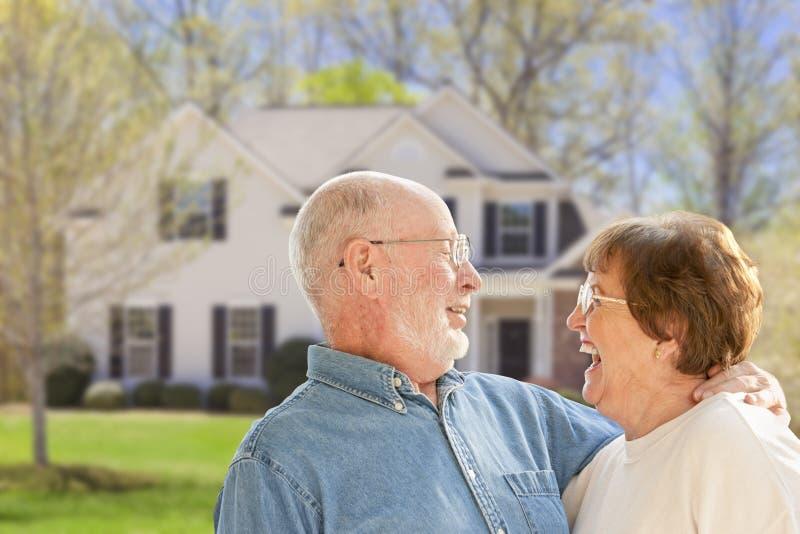 Glückliche ältere Paare in Front Yard des Hauses lizenzfreie stockfotos