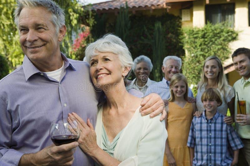 Glückliche ältere Paare mit dem Arm herum stockbild