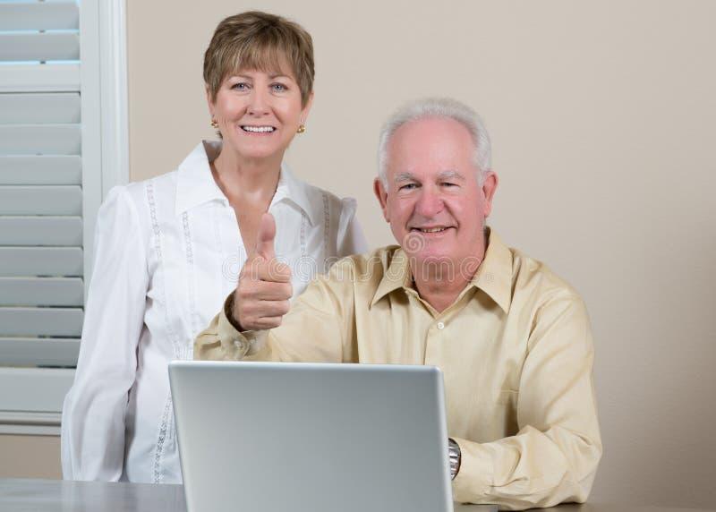 Glückliche ältere Paare mit dem Laptop, der Daumen aufgibt lizenzfreie stockbilder