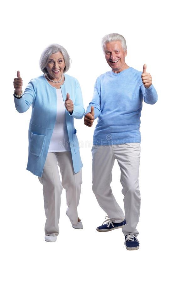 Glückliche ältere Paare mit den Daumen oben auf weißem Hintergrund stockfoto