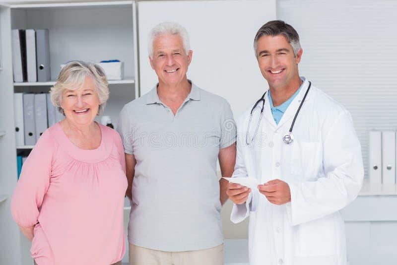 Glückliche ältere Paare mit Doktor, der in der Klinik steht stockfotos