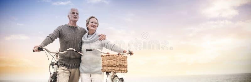 Glückliche ältere Paare mit ihrem Fahrrad lizenzfreie stockbilder