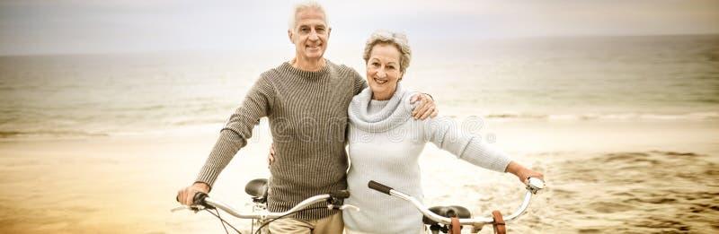 Glückliche ältere Paare mit ihrem Fahrrad lizenzfreies stockbild