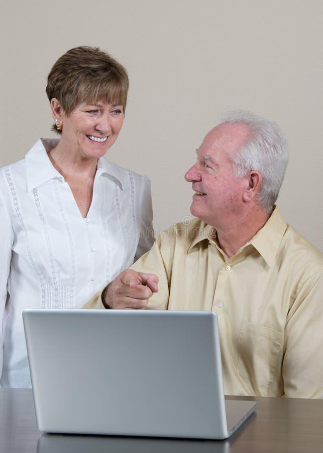 Glückliche ältere Paare mit Laptop zeigen auf Schirm stockbilder