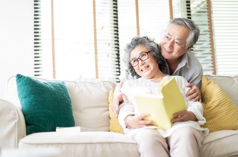 Glückliche ältere Paare sitzen auf der Couch zusammen und lesen ein Buch und schauen seitlich im Wohnzimmer zu Hause lizenzfreie stockfotografie