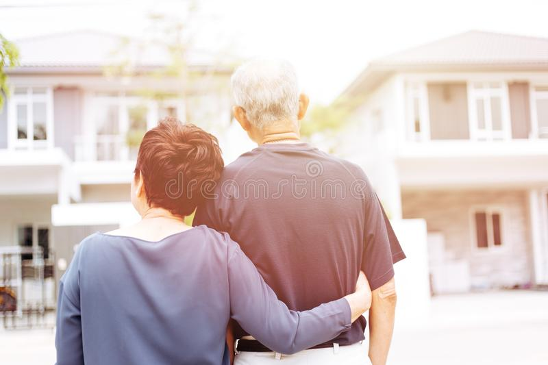 Glückliche ältere Paare von hinten schauendes Vorderhaus und Auto Warmer Ton mit Sonnenlicht lizenzfreies stockbild
