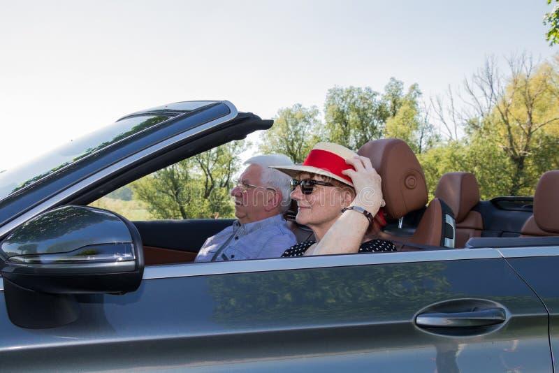Glückliche ältere Seniorpaare mit dem Luxusauto lizenzfreies stockbild