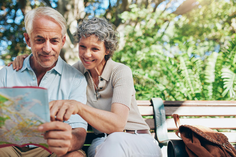 Glückliche ältere touristische Lesekarte lizenzfreie stockfotos