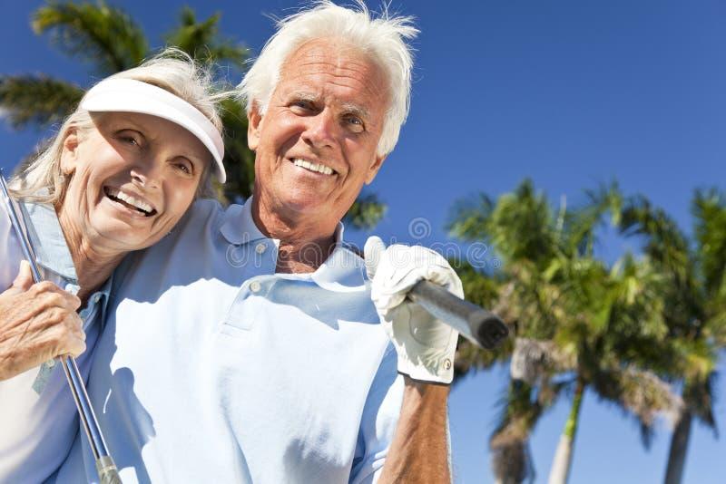 Glückliche älterer Mann-u. Frauen-Paare, die Golf spielen stockbild