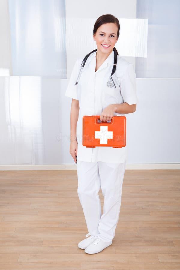Glückliche Ärztin, die Kasten der ersten Hilfe hält stockfoto
