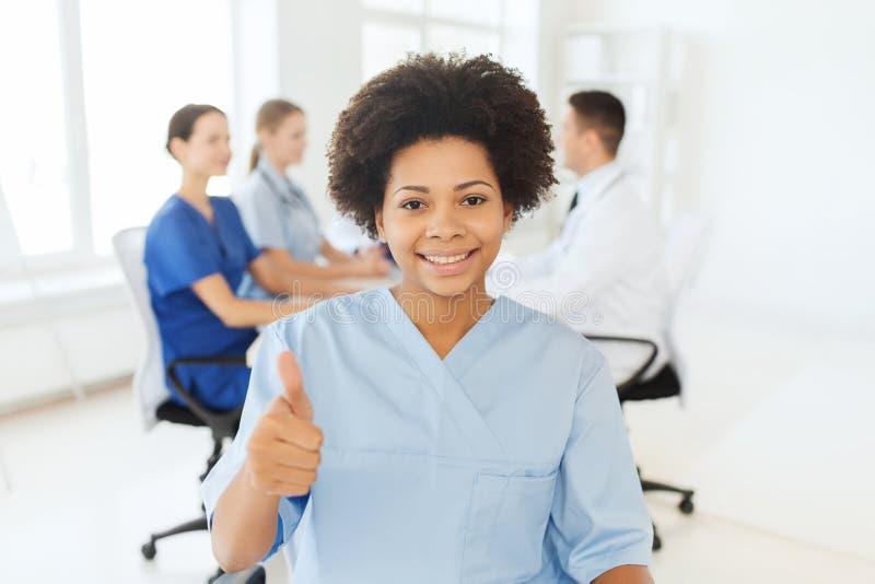 Glückliche Ärztin oder Krankenschwester, die sich Daumen zeigen stockfotos