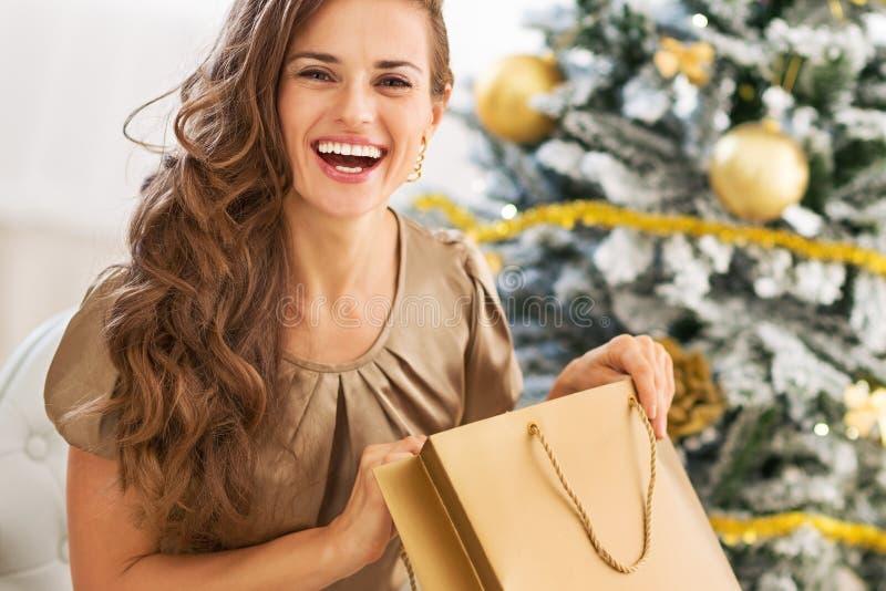 Glückliche Öffnungseinkaufstasche der jungen Frau nahe Weihnachtsbaum stockfotografie