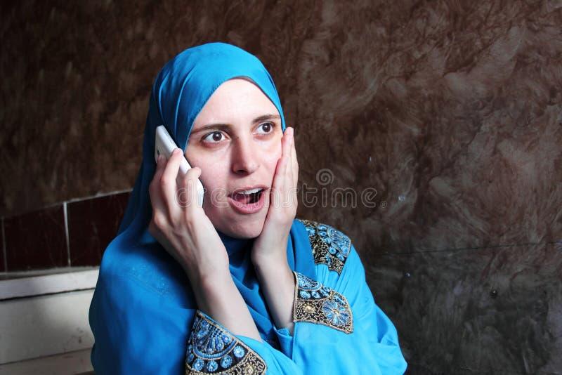 Glückliche überraschte arabische moslemische Frau mit Mobile lizenzfreies stockfoto