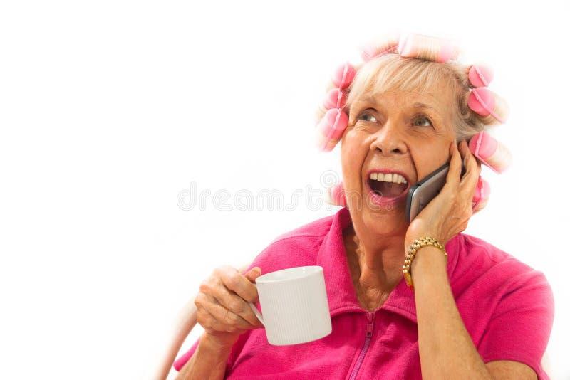 Glückliche, überraschte Dame in den Lockenwicklern auf Handy lizenzfreies stockbild