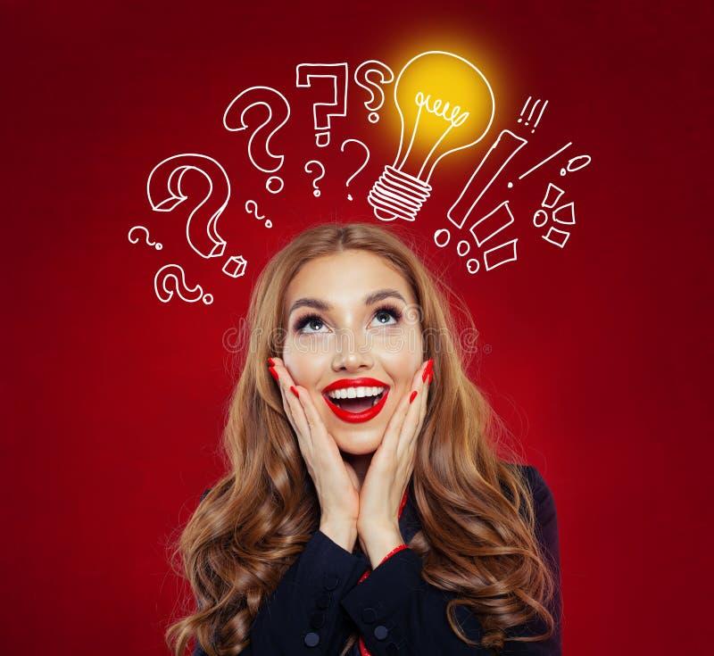 Glückliche überraschte Frau, die oben gelber Glühlampe auf rotem Hintergrund betrachtet Geistesblitz, Ideen, Problem und Lösungsk lizenzfreies stockbild