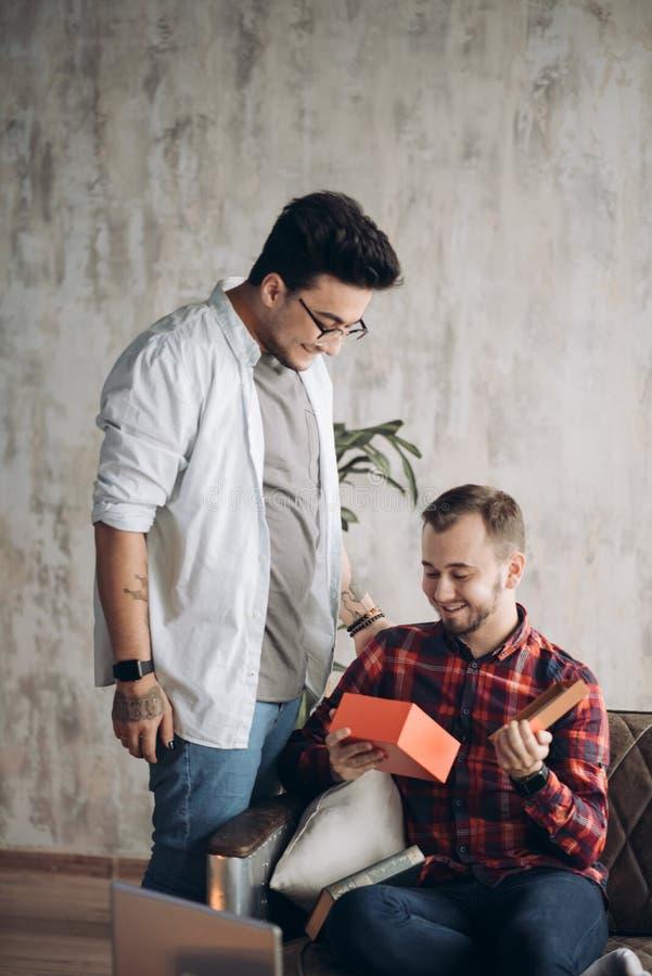 Glückliche überraschte junge hübsche homosexuelle Paare, die zu Hause Geschenk feiern und geben lizenzfreies stockfoto
