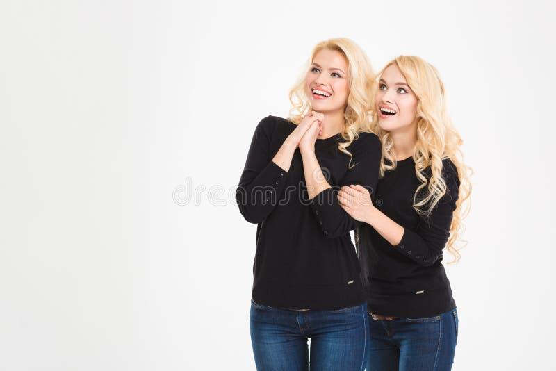 Glückliche überraschte Schwesterzwillinge, die auf etwas schauen stockfotografie
