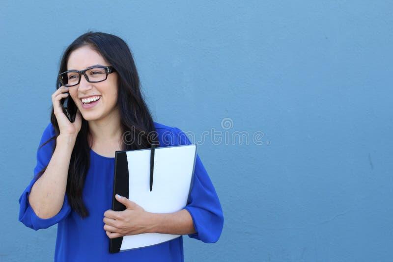 Glückliche überzeugte Geschäftsfrau, die am Mobilhandy lokalisiert auf Blau spricht lizenzfreie stockfotografie