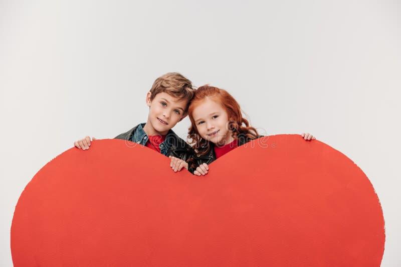 glückliche Abbindenkleinkinder hinter großem rotem Herzen lizenzfreies stockfoto