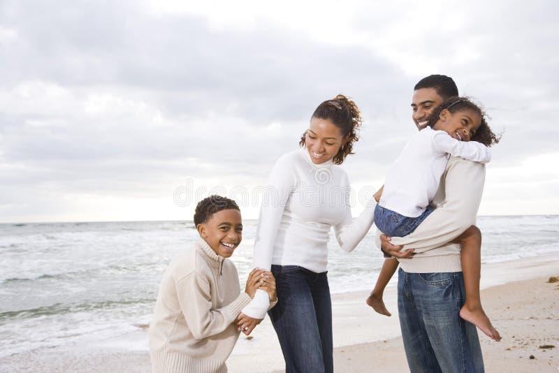 Glückliche African-Americanvierköpfige Familie auf Strand stockfoto