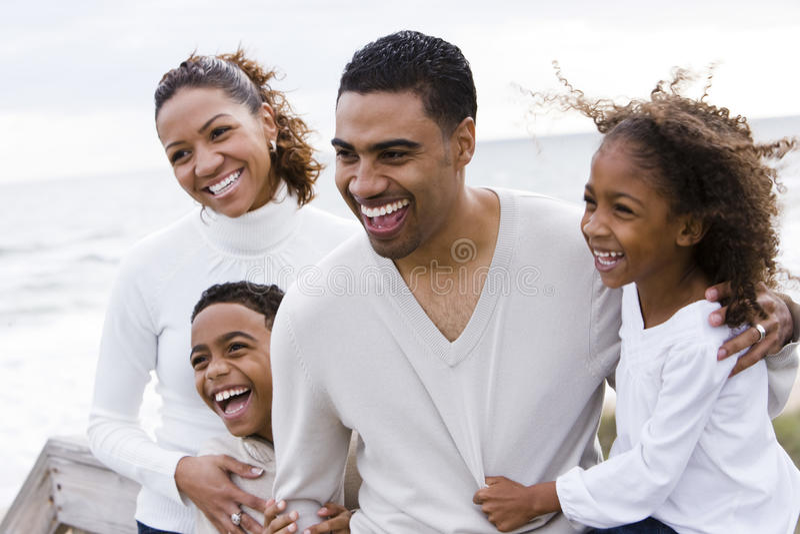 Glückliche African-Americanvierköpfige Familie auf Strand stockfotografie