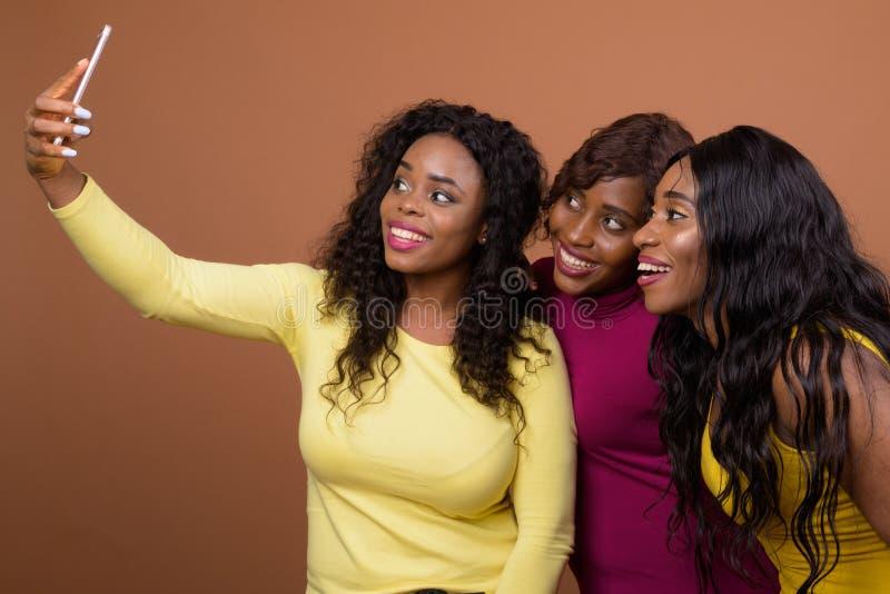 Glückliche Afrikanerinnen, die Selfie mit Handy nehmen stockbilder