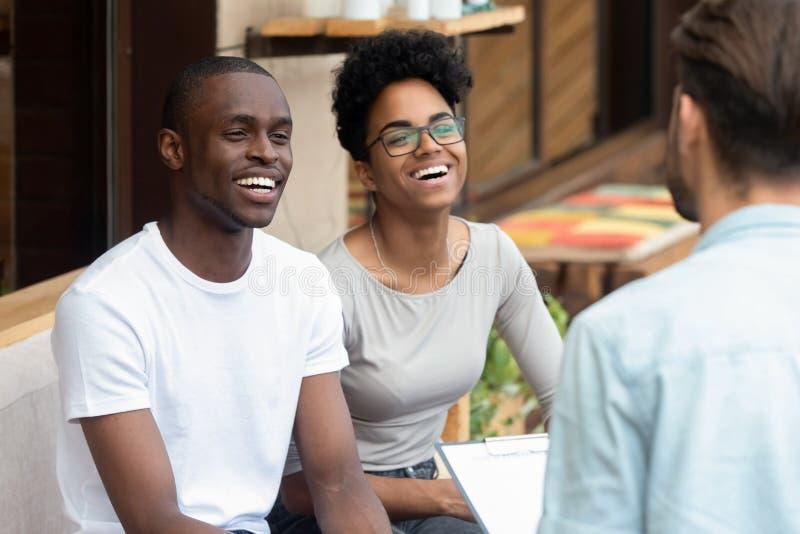 Glückliche afrikanische Familienpaare hören auf Ratgeberpsychologen, Kunden zu konsultieren lizenzfreies stockbild