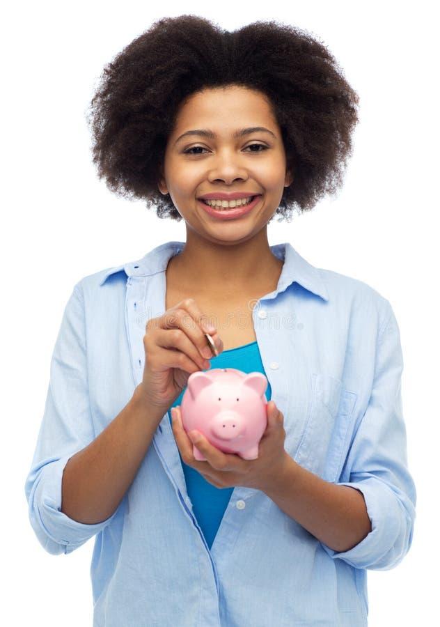 Glückliche afrikanische Frau, die Münze in Sparschwein setzt lizenzfreie stockfotos