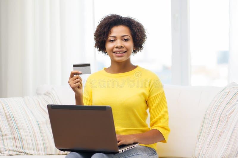 Glückliche afrikanische Frau mit Laptop und Kreditkarte stockbilder