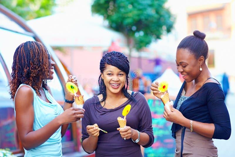 Glückliche afrikanische Freunde, die draußen Eiscreme essen lizenzfreie stockbilder