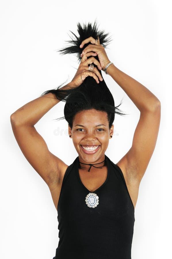Glückliche afrikanische Mädchenholding ihr Haar stockbild