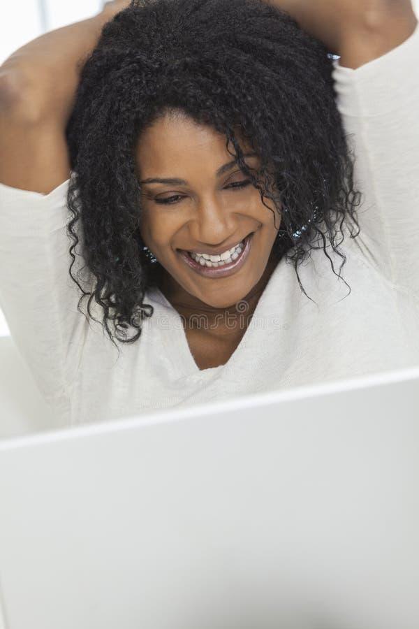 Glückliche Afroamerikaner-Frau, die Laptop-Computer verwendet stockfotos