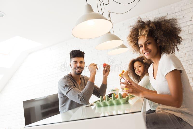 Glückliche Afroamerikanerfamilie, die Ostereier färbt stockbild