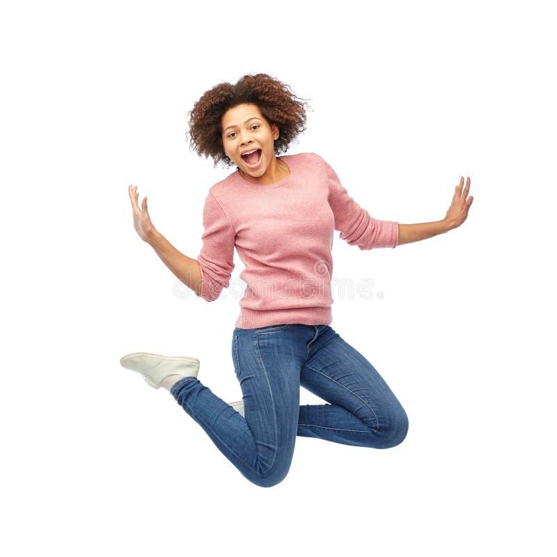 Glückliche Afroamerikanerfrau, die über Weiß springt stockbilder