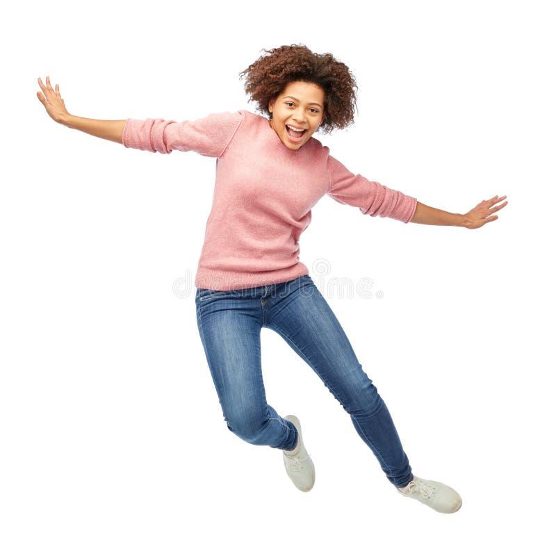 Glückliche Afroamerikanerfrau, die über Weiß springt stockfotos