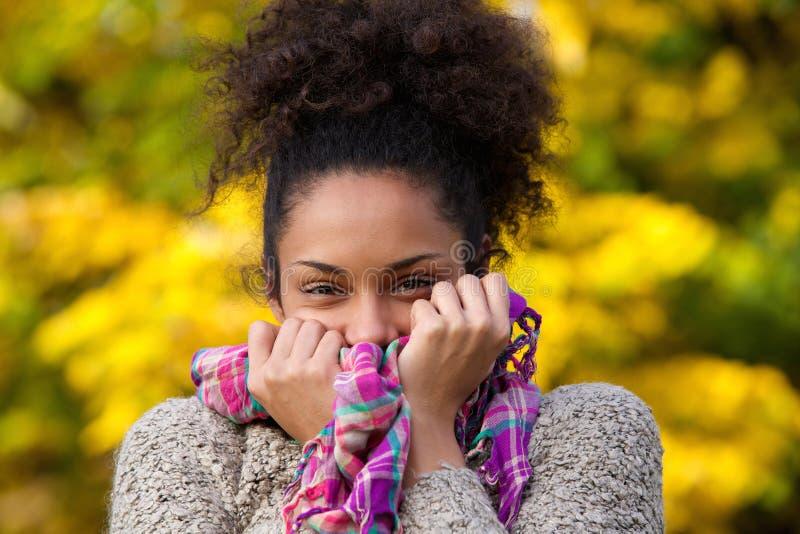 Glückliche Afroamerikanerfrau, die mit Strickjacke und Schal aufwirft lizenzfreie stockfotografie