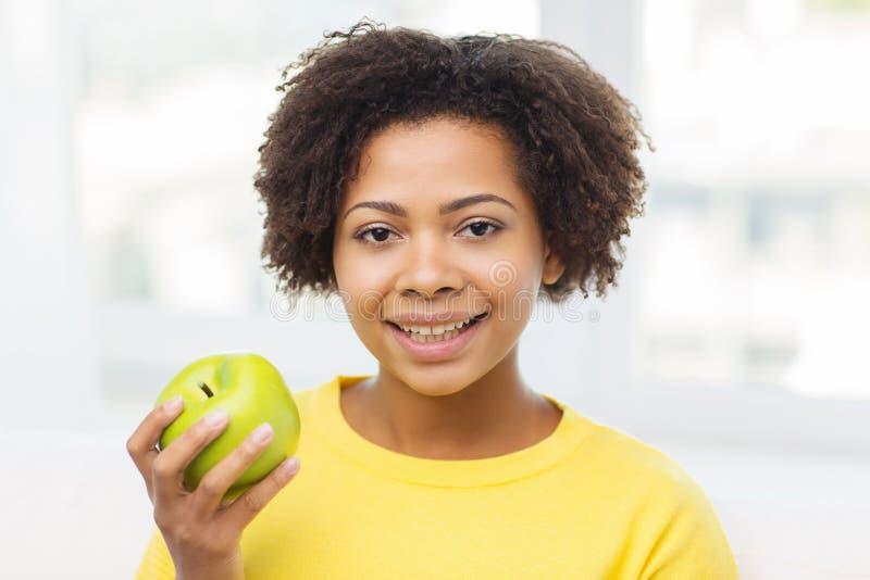Glückliche Afroamerikanerfrau mit grünem Apfel lizenzfreie stockfotos