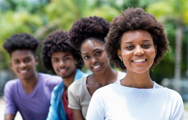 Glückliche Afroamerikanerfrau mit Gruppe jungen Erwachsenen in der Linie stockfoto