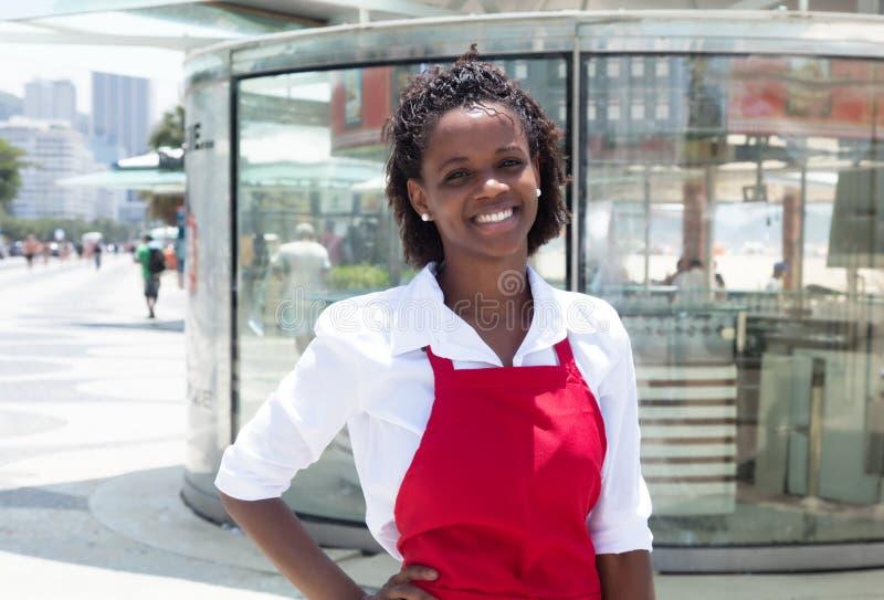 Glückliche Afroamerikanerkellnerin vor dem Restaurant stockbild