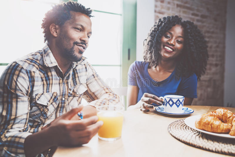Glückliche Afroamerikanerpaare frühstücken zusammen morgens am Holztisch Junger schwarzer Mann und seiner stockfoto