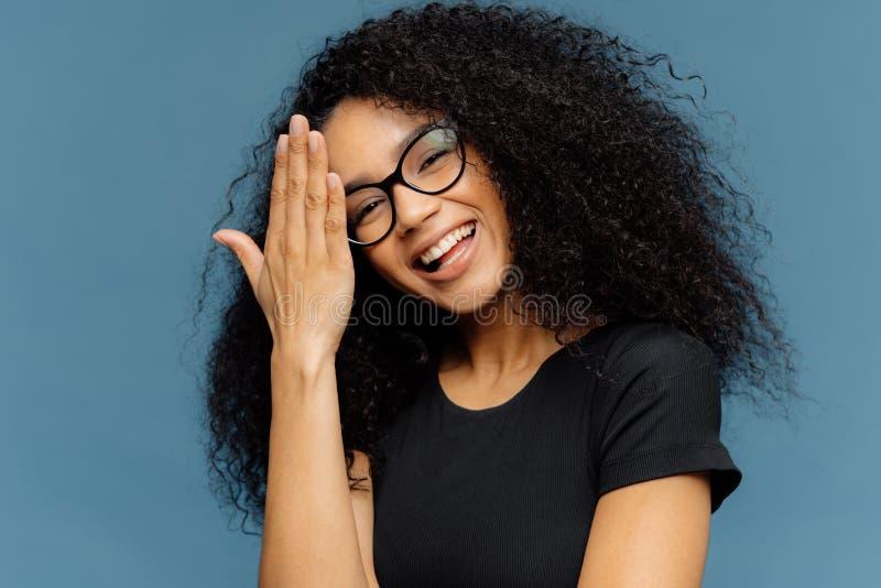 Glückliche afroe-amerikanisch Frau berührt Stirn, kippt Kopf, lächelt glücklich an der Kamera, hat den Innen Spaß, trägt optische stockbilder