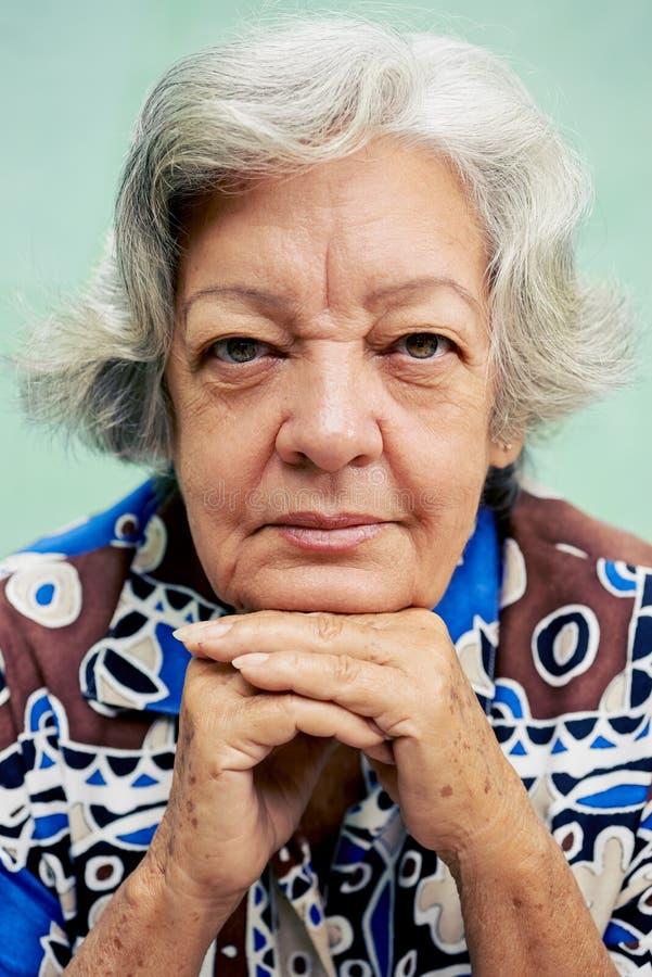 Glückliche alte Frau, die Kamera lächelt und betrachtet stockfoto