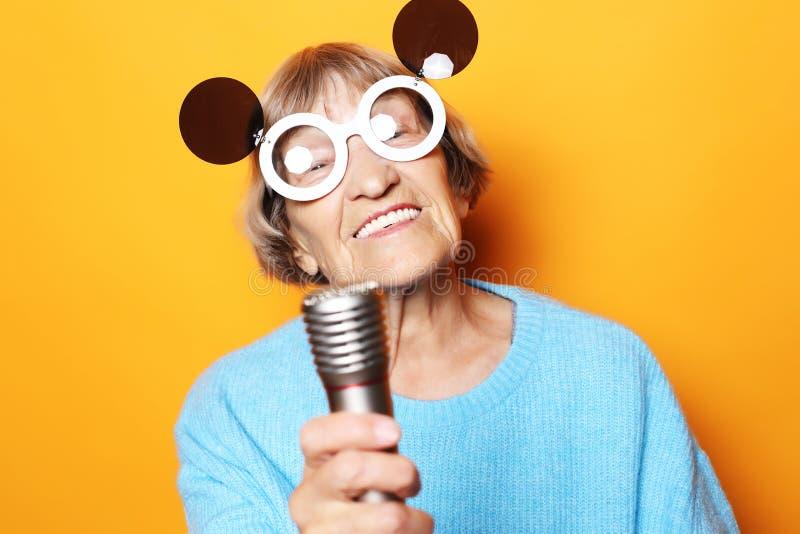 Glückliche alte Frau mit den großen Brillen, die ein Mikrofon und einen Gesang lokalisiert auf gelbem Hintergrund halten stockbilder