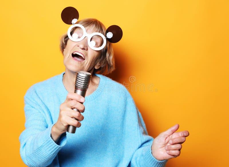 Glückliche alte Frau mit den großen Brillen, die ein Mikrofon und einen Gesang lokalisiert auf gelbem Hintergrund halten lizenzfreie stockfotografie