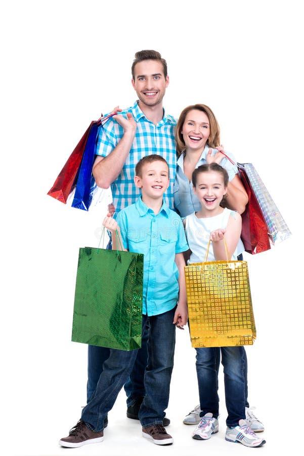 Glückliche amerikanische Familie mit den Kindern, die Einkaufstaschen halten lizenzfreie stockbilder
