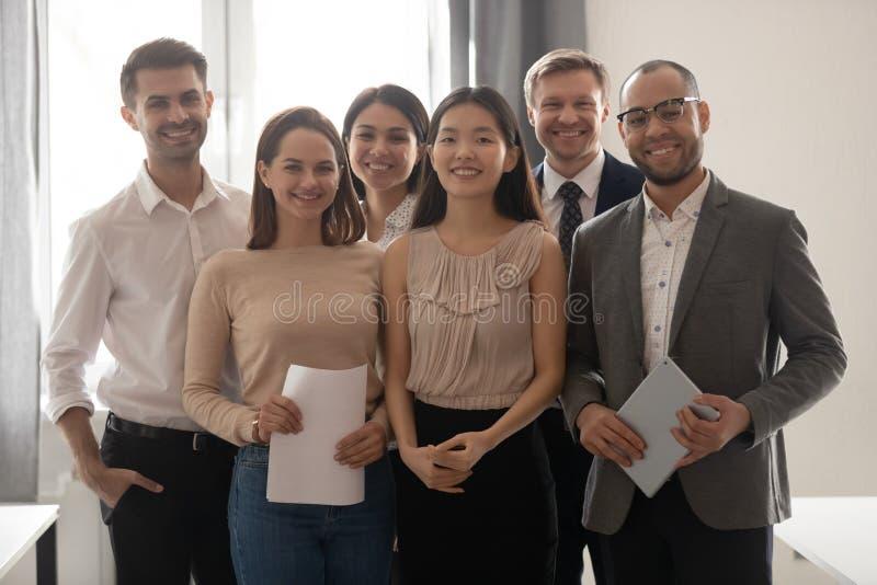 Glückliche Angestelltgruppe des multikulturellen Berufsarbeitsteams, die Kamera betrachtet stockbild