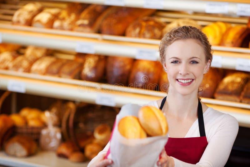 Glückliche Arbeitnehmerin, die Tasche von Broten gibt lizenzfreies stockfoto